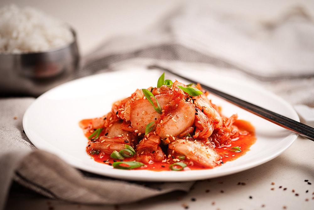 Kimchi - Ensalada picante de col y verduras maceradas.La comida por excelencia de la cultura culinaria Coreana que todo iniciado a la comida coreana debería probar.Col china, zanahorias, ajo, jengibre, cebolleta, sésamo, sal, todo mezclado en una proporción adecuada junto con polvo de guindilla y salsa de pescado.5.00€