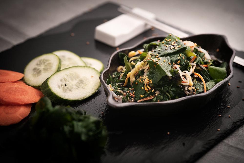 Miyokmuchim - Ensalada fresca a la vinagreta de algas.Ensalada con algas frescas a la vinagreta agridulce, con sésamo, ajo y pepino (ó zanahoria).Una ensalada muy saludable con un profundo aroma a mar.5.50€