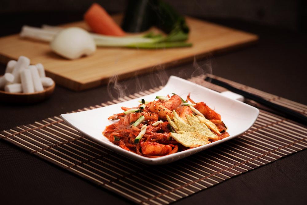 Tokbokki - Pasta de arroz con pastel de pescado y verduras con salsa de guindilla.Plato callejero típico y popular coreano, amado por todos los coreanos.Plato dulce y picante a la vez con una textura suave de pasta gruesa de arroz y el sabor suave de pastel de pescado en láminas finas.11.90€