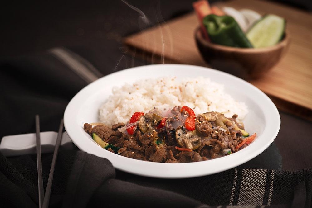 Bulgoguibab - Plato combinado de Bulgogui con arroz blanco.Bulgogui es el plato coreano de carne por excelencia. Ternera en finas láminas marinada con salsa dulce de soja y frutas (manzana, pera coreana) y verduras variadas cocinadas a fuego lento, con el acompañamiento perfecto del arroz blanco.12.90€