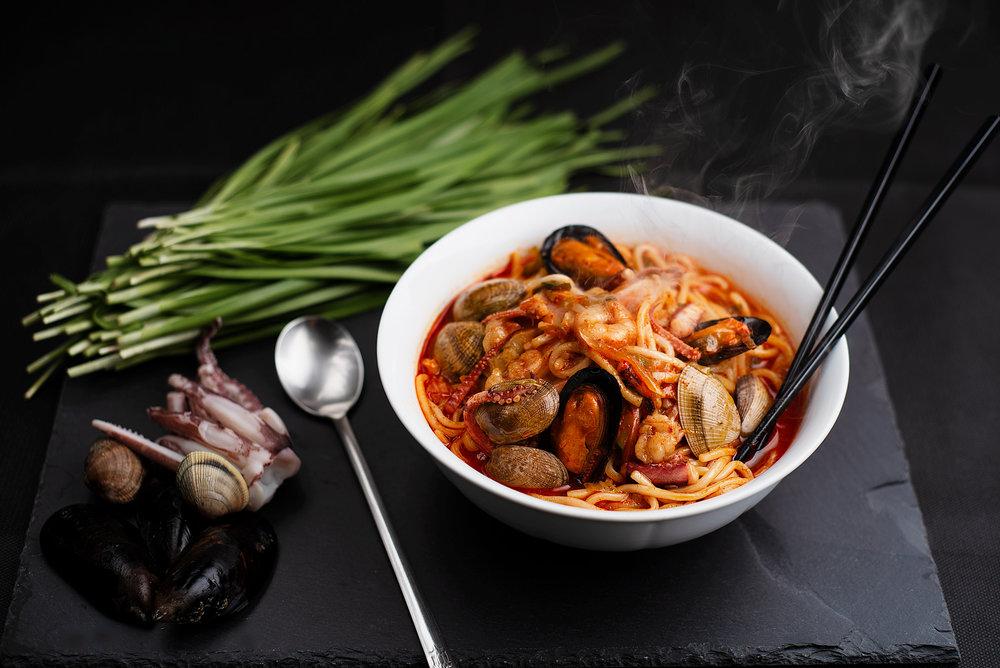 Champong - Tallarines picantes de marisco variado.Tallarines gruesos de harina en caldo de verduras caliente y picante de guindilla, con mariscos variados (calamares, almejas, gambas) y verduras variadas. Un sabor a mar que te sorprenderá de una forma nueva.12.90€