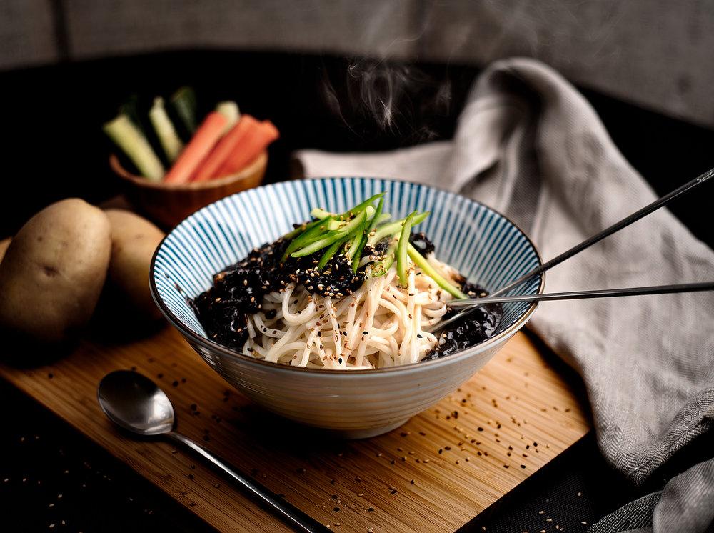 Chajangmyun - Tallarines a la pasta de soja densa.Plato de tallarines curioso por su salsa negra y densa de soja.Pasta gruesa de harina, salsa dulce de pasta de soja densa, cebolla, zanahorias, carne de cerdo, calabacín en combinación, con un aspecto y sabor de otro mundo.11.90€