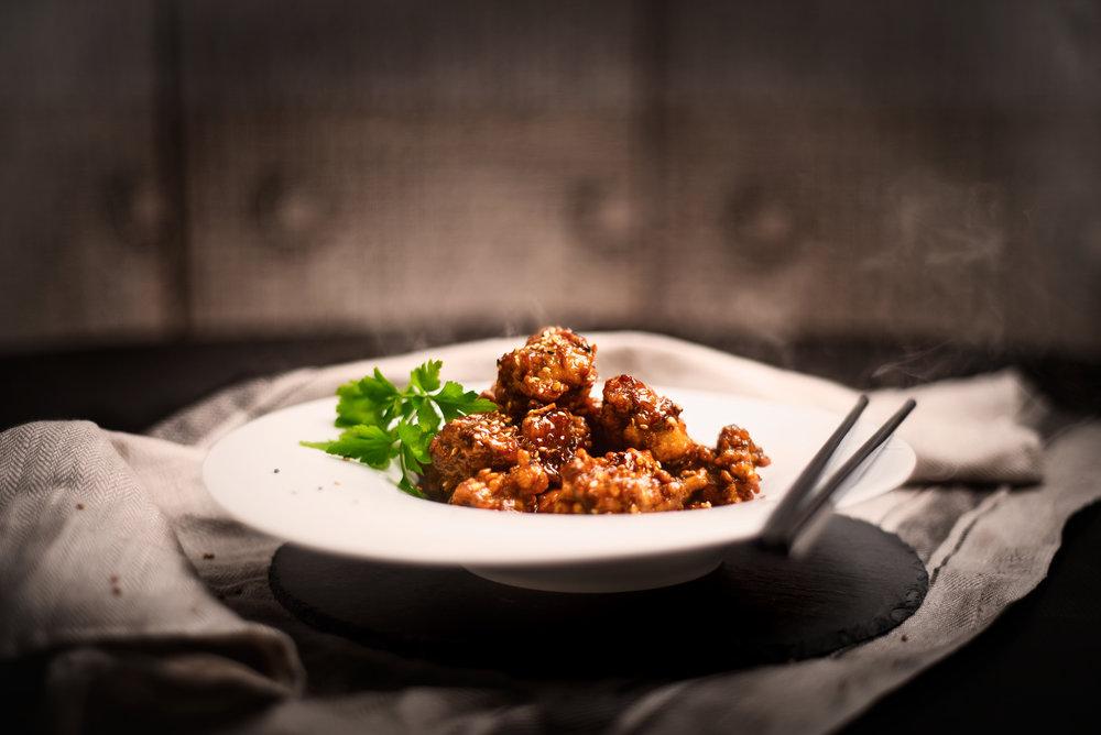 Dakgangjong - Bolas de pollo recubierto de salsa dulce de soja y miel.Otro de los platos callejeros típicos de Corea de gran popularidad.Crujiente cubierta de fritura con salsa de soja y miel por fuera, y jugosa carne de pollo por dentro, con topping de trozos de cacahuete tostado. Dulce, salado y con un toque de canela, el pollo como nunca lo has probado.