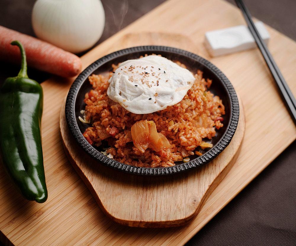 Kimchi bokumbab - Arroz frito de kimchi.El arroz frito más coreano posible, con kimchi, carne de cerdo, verduras, coronado con un huevo frito.8.90€