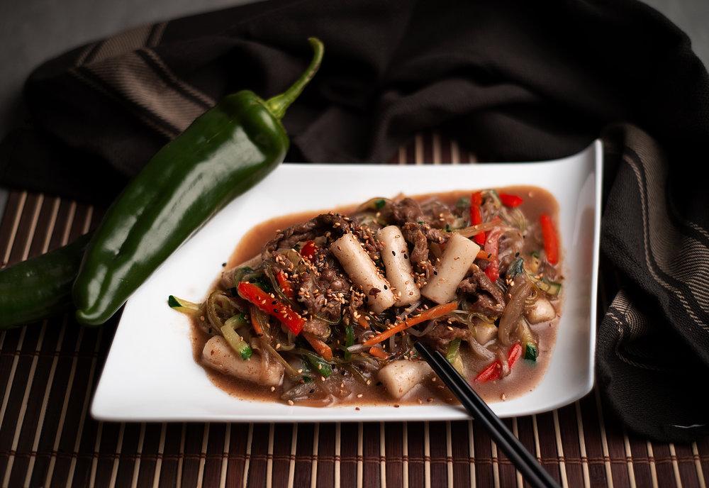 Bulgogui Tokbokki - Bulgogui con pasta de arroz blanco.Carne de ternera con verduras y fideos de fécula de batata, cocinada con salsa especial dulce de soja.La combinación del plato de ternera por excelencia de la cocina coreana junto con la pasta de arroz para aportar textura y consistencia a un plato de por sí ya perfecto.12.90€