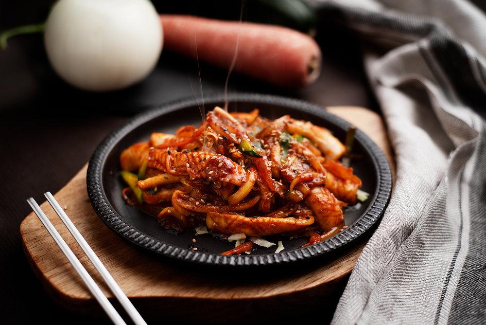 Ojingobokum - Plancha de calamares y verduras a la salsa de guindilla.Calamares en tiras, cebolla, ajo, cebolleta, zanahoria y verduras varias cocinado en salsa de soja y guindilla, y servido en plato de acero caliente.14.50€