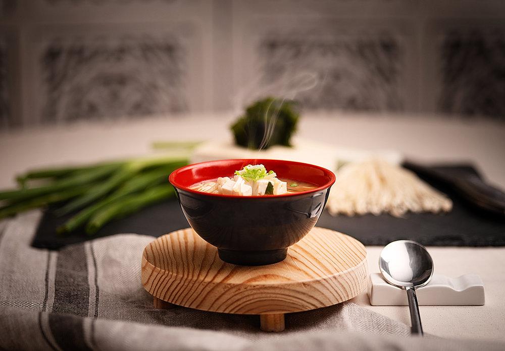 Sopa de Miso - Sopa caliente de miso(pasta fermentada de soja) con cuadrados de tofu suave, cebolletas, ajo y chirlas en caldo de verduras.