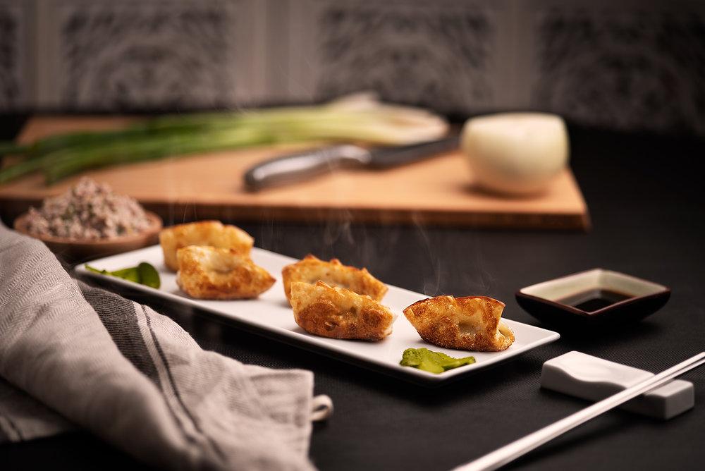 Mandu - Empanadillas coreanas fritas.Empanadillas de carne de cerdo y verduras condimentadas y fritas, servidas con salsa de soja.