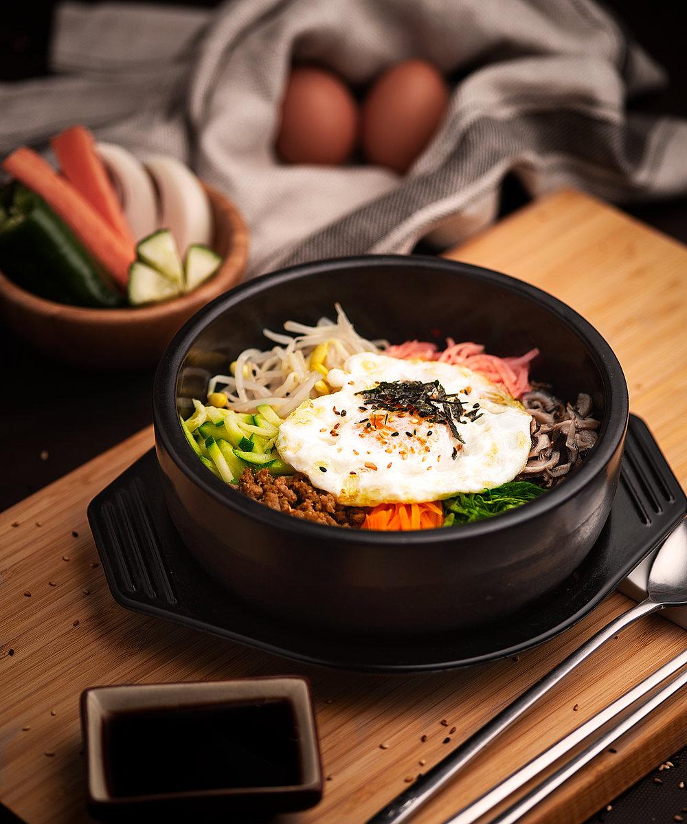 Dolsot Bibimbab - Cuenco de piedra ardiente con arroz blanco de base coronada con verduras variadas rehogadas, y con un huevo frito aderezado todo con virutas de algas y sésamo.