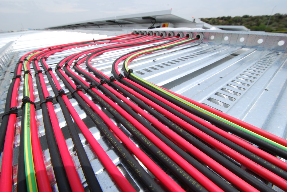 Example: iEnergytech supplies Swiss-made Huber+Suhner DC cable on all its installs. This RADOX cable is fire resistant and has an 8x longer lifetime than XLPE. Its rigid outer structure provides added security during installation work. Photo shows cable work at the 100kWp Holmwood Group installation.