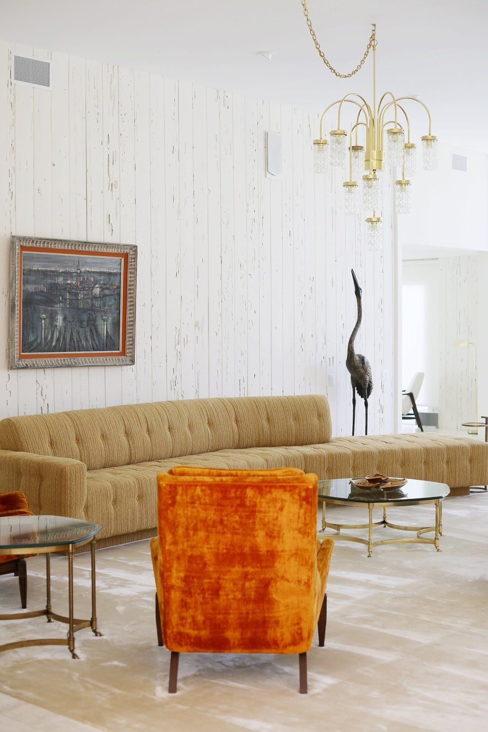Couch by  Elrod , painting by  Regis Bouvier de Cachard  which is from Frank Sinatra's office in the 1960s, orange chair by  Adrian Pearseall .