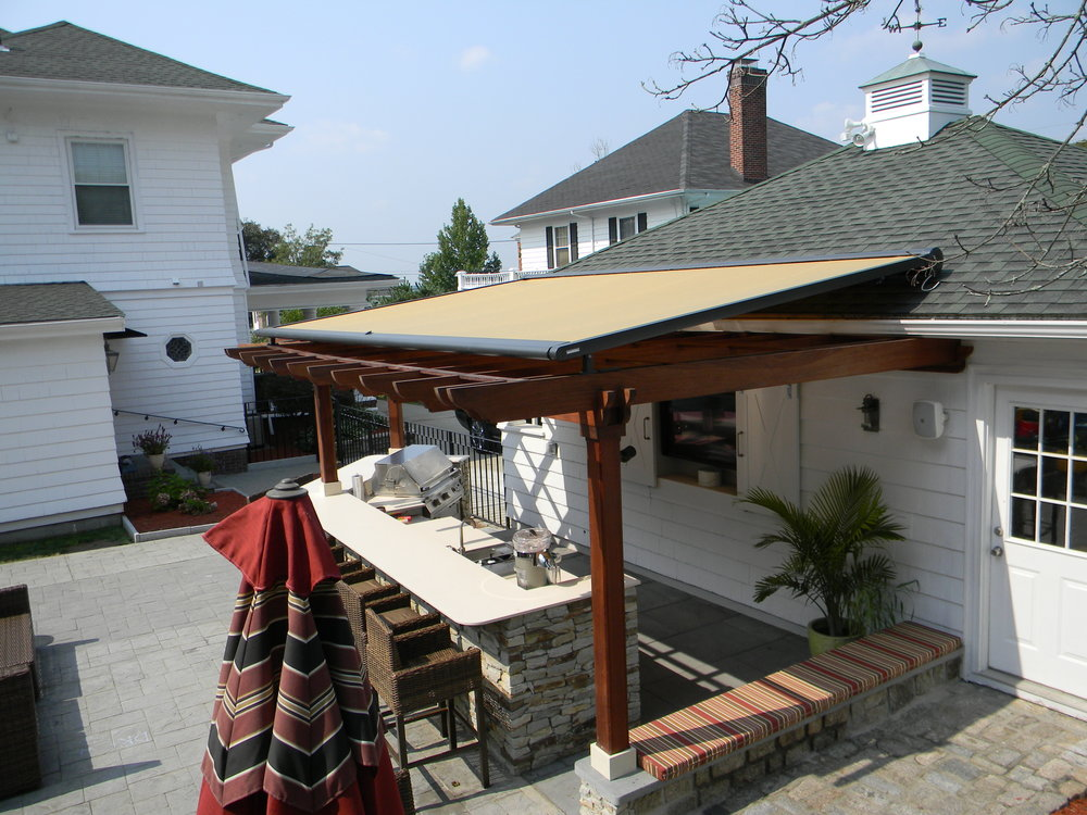 Project: Custom Kitchen w/ Markilux M8800 retractable canopy mounted on a Mahogany Pergola. Custom manufactured cushion and built in A/V.