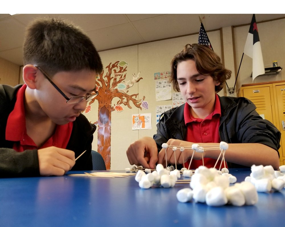 Two 7th and 8th graders in the process of building their toothpick and marshmallow structures for Physical Science.