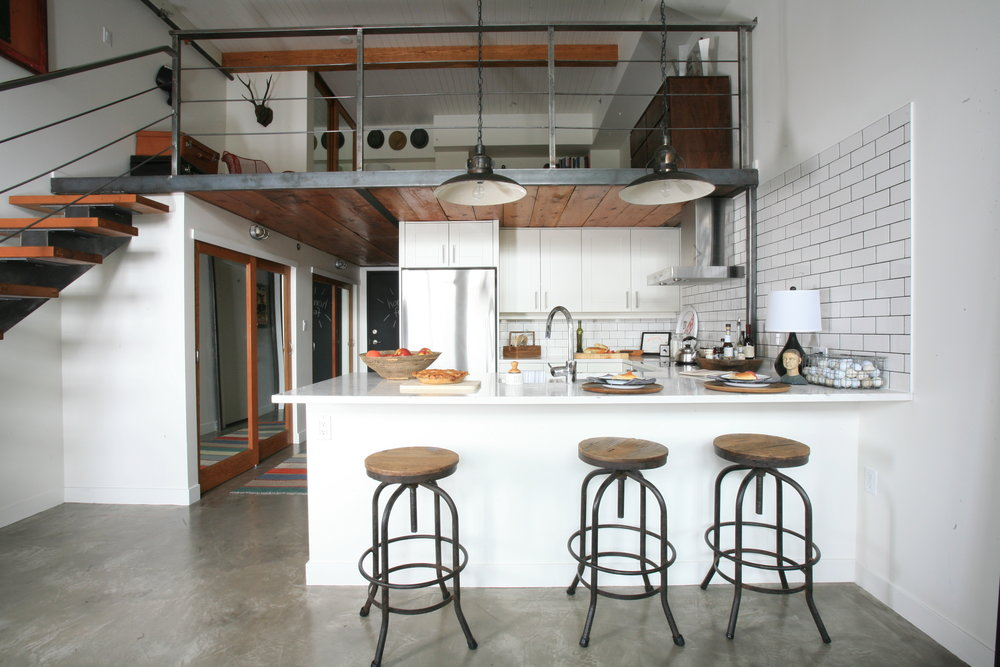 A modern kitchen with modern appliances and fixtures with wooden barstools under the counters, and various kitchen accoutrements such as a pie, a wooden tray with various bottles and a basket full of white balls.