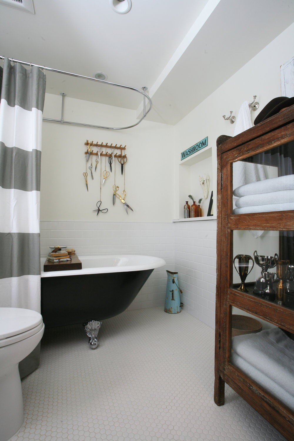 This white tiled bathroom features a black matte free standing claw foot tub with a grey and white shower curtain hanging around it. On the wall behind it is a decorative wooden hook with various scissors tied to it with ribbon and located in the foreground there is a wood and glass cabinet that houses towels and trophies.