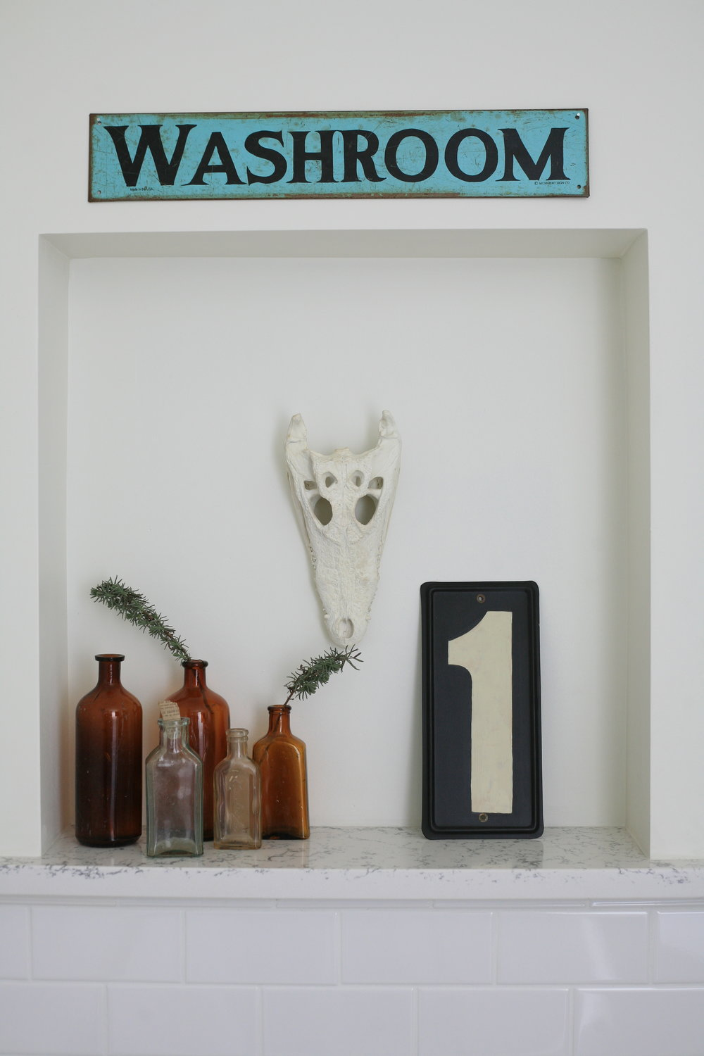 "Various clear and brown jars with herbs sticking out of it, an animal skull and a sign that says ""1"" sit in a white alcove and a blue sign hangs above it that reads ""Washroom""."