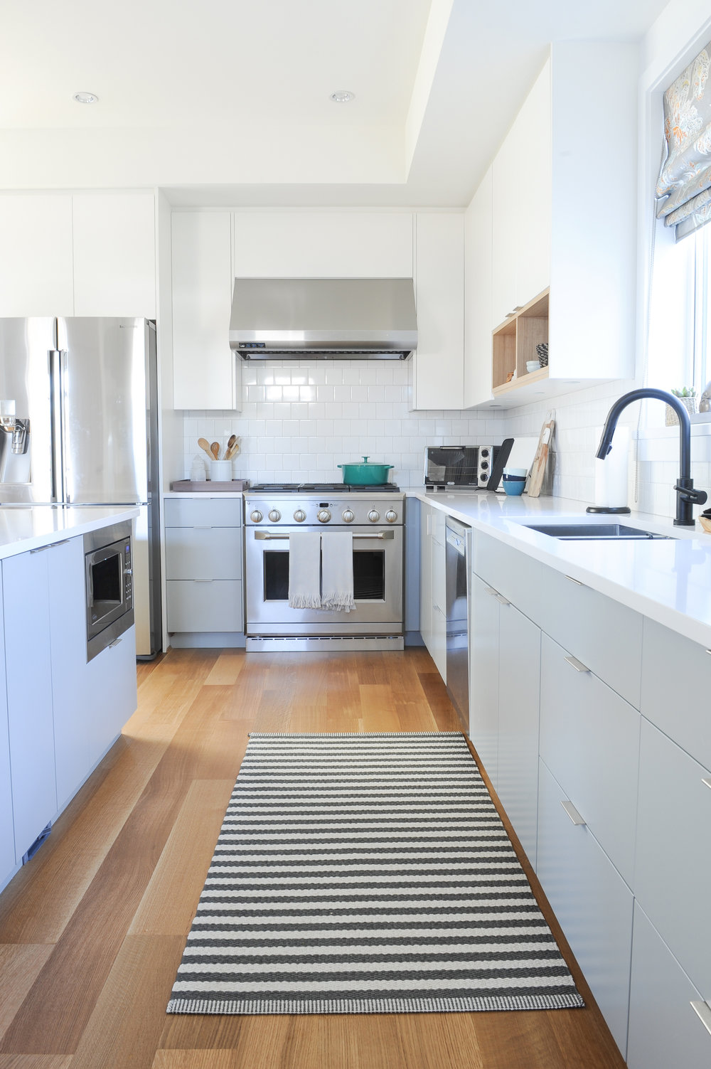 A large striped carpet sits on beautiful hardwood floors in a bright and modern kitchen complete with a matte black faucet, large steel range hood, and gas stove.