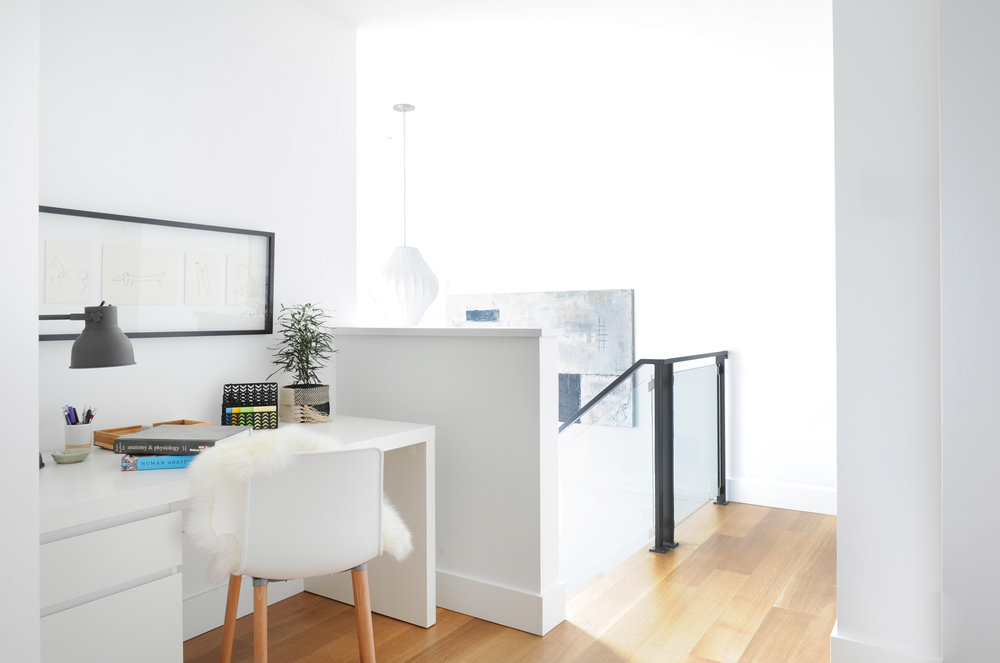 At the top of the stairs sits a home office with desk and chair.