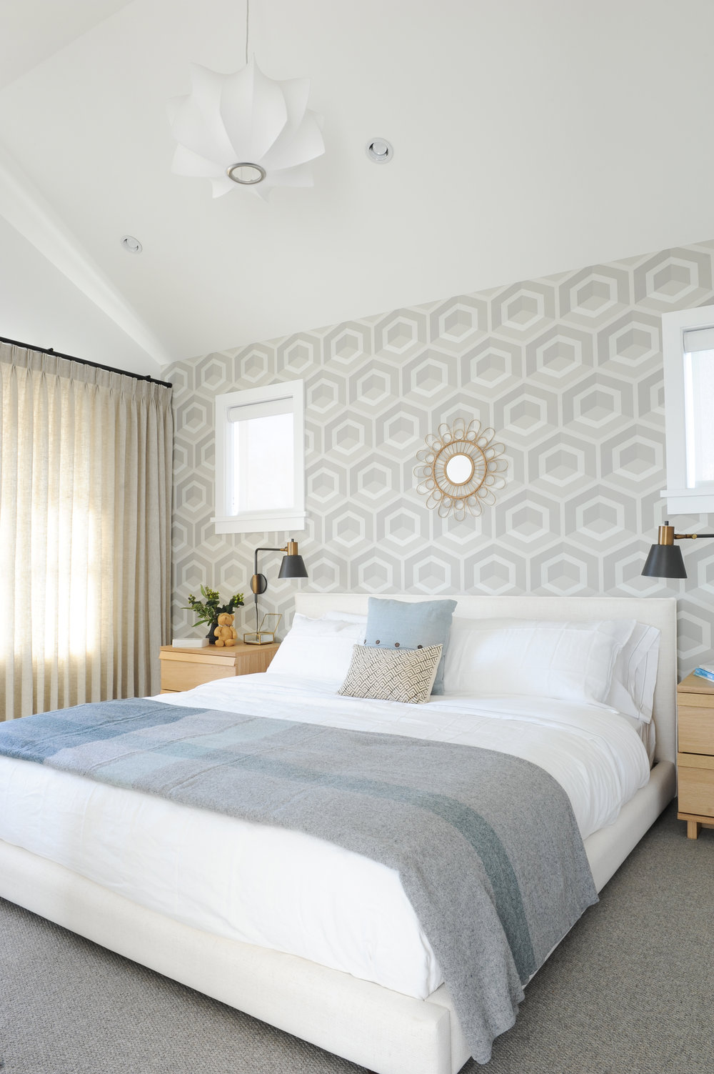 A bedroom with a white bed and two side tables sit in front of a bright honeycomb wallpaper and mirror on the wall