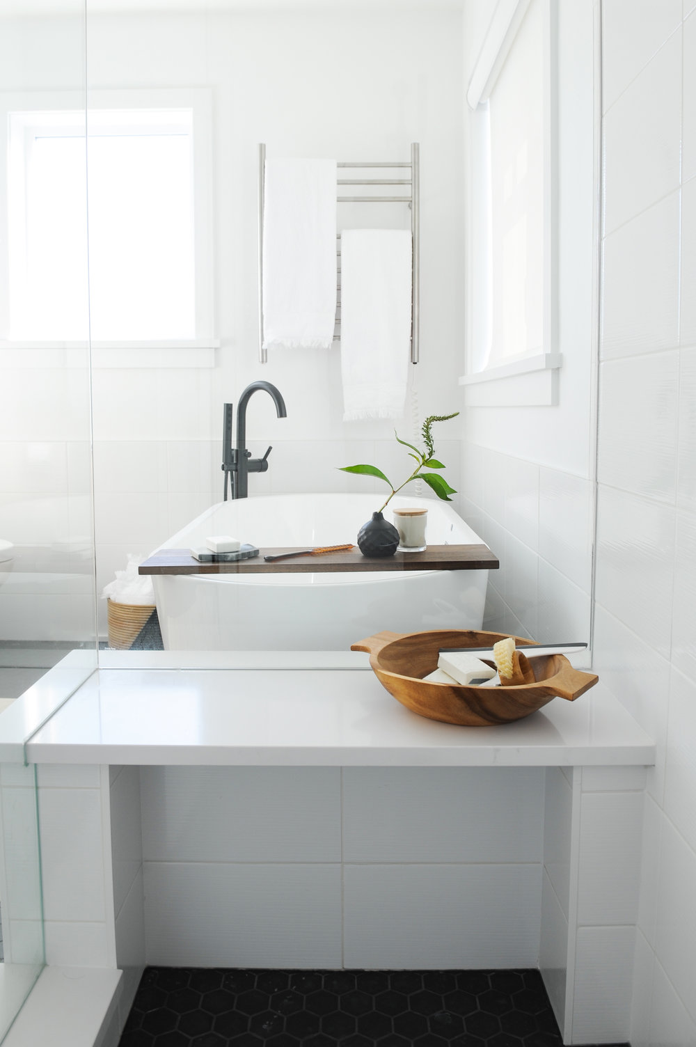 A beautiful tub sits in the background of a bright modern bathroom and a shower bench is pictured in the foreground.