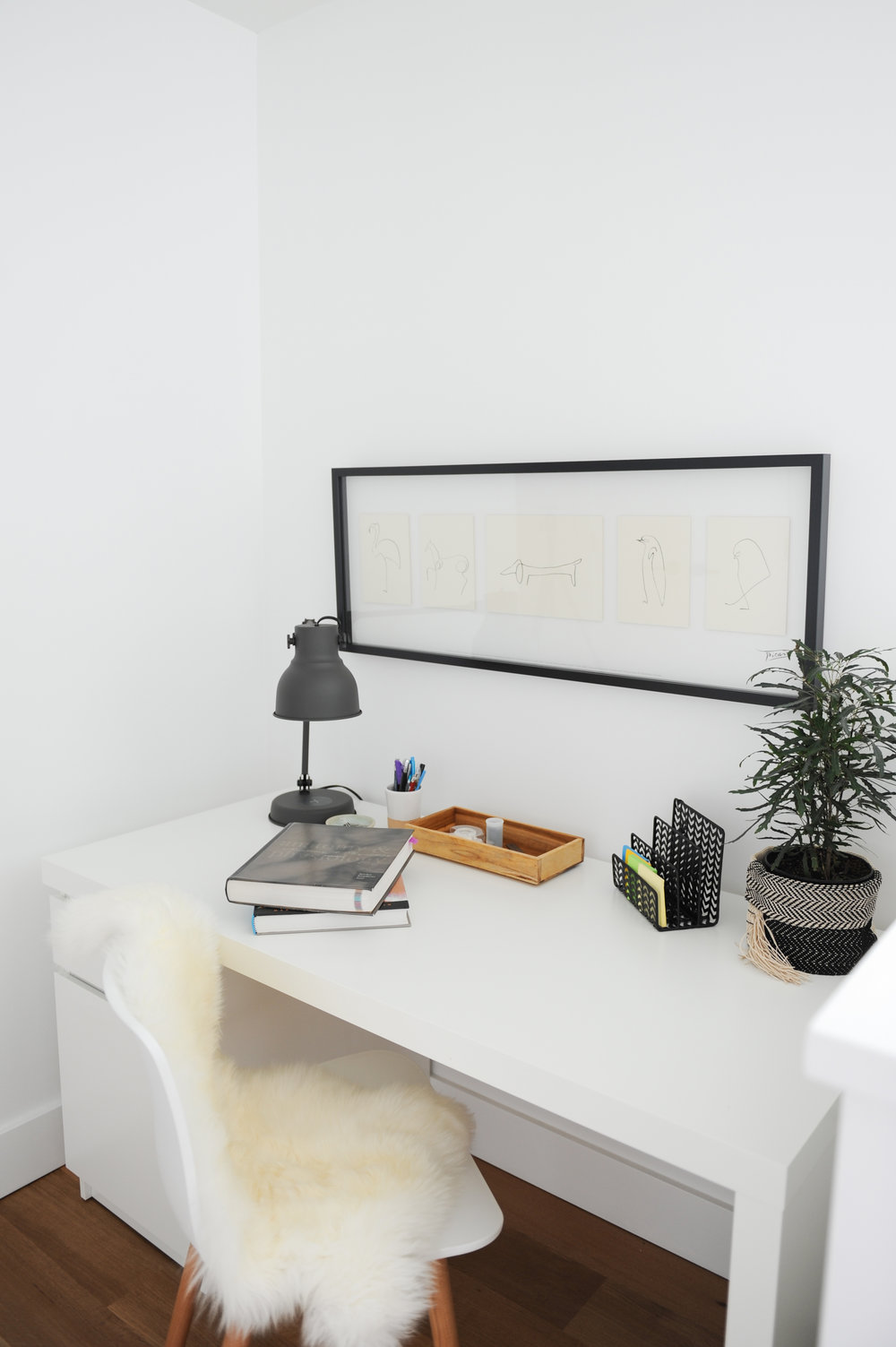 A home office set up, including a white chair with a sheep skin rug draped over it and a white desk with various office supplies such as books and desk lamp sits in front of a large frame.