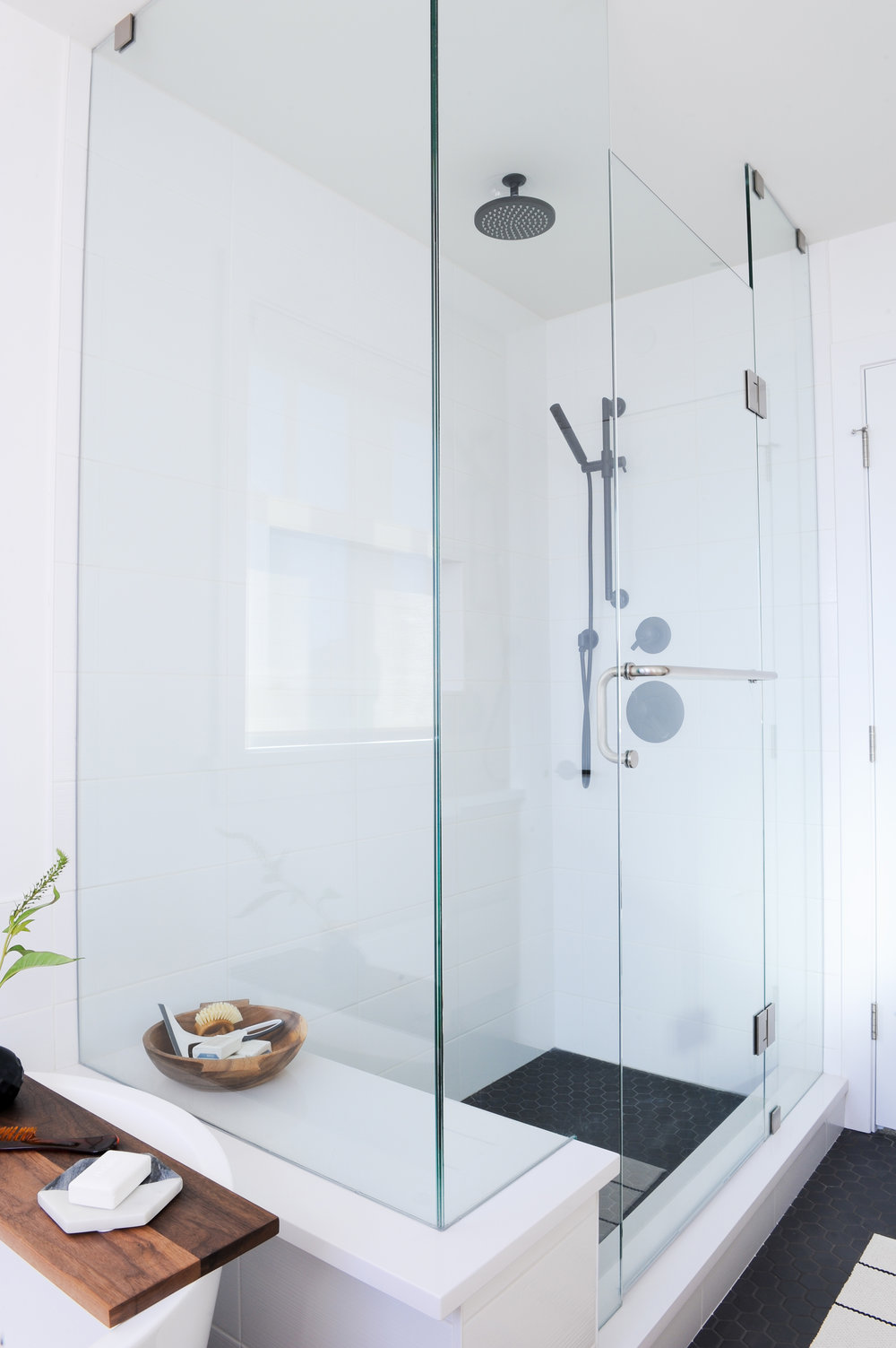 A stand up shower with rain shower attachment and glass walls