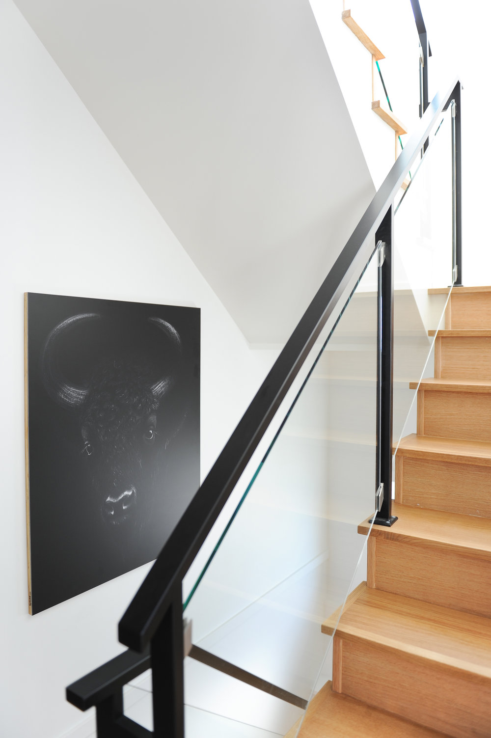 A black and white picture of a bovine hangs on the hallway walls next to a wooden staircase with glass railings.