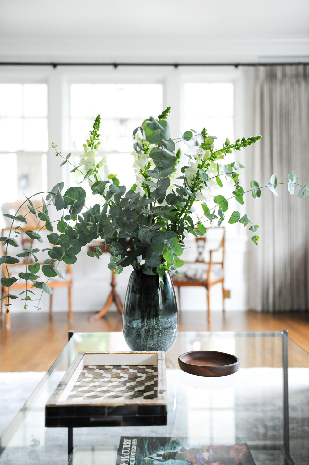 A vase with green plants, a wooden tray and a wooden ashtray sit on a glass coffee table.