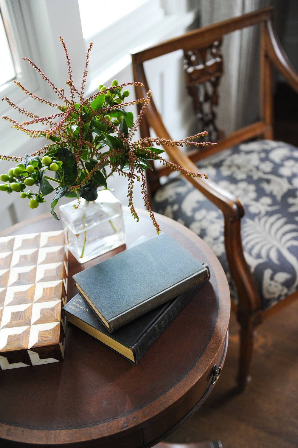 A wooden chair with a blue and white upholstered seat sits next to a small round table. There is a little square glass vase with plants sitting next to two books and a rectangular wooden box top.
