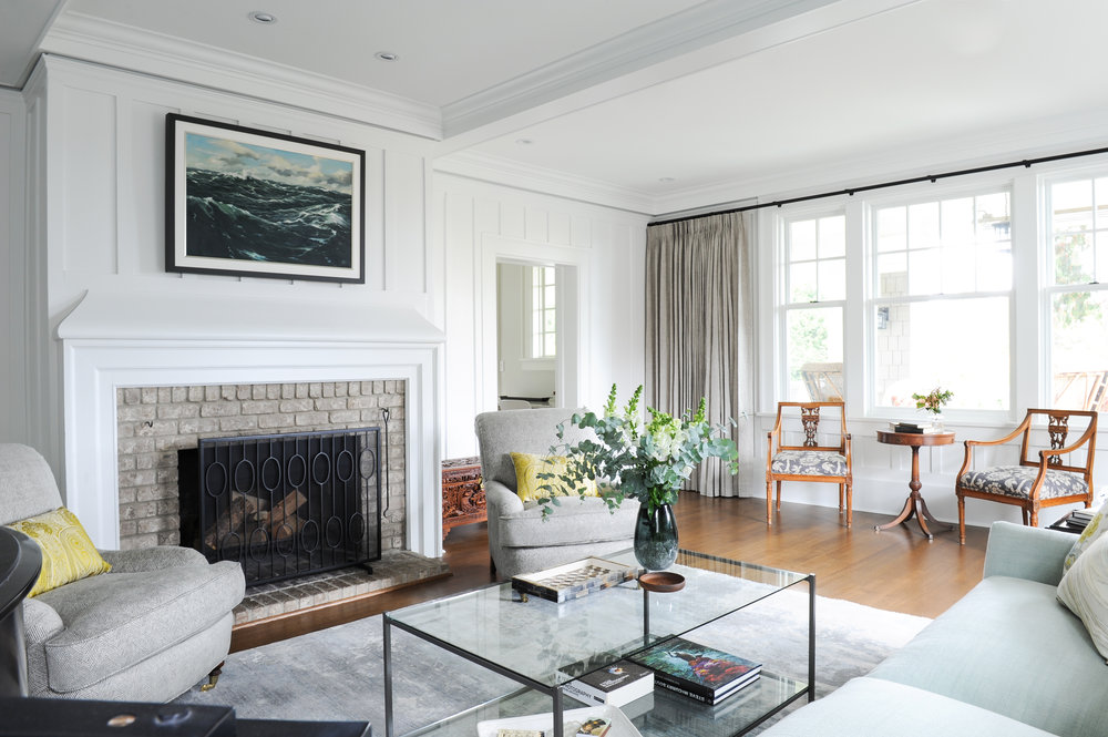 A living room with a love seat and two armchairs surrounding a glass coffee table. There is a brick fireplace built into the white walls and a large painting of the sea hangs above it.