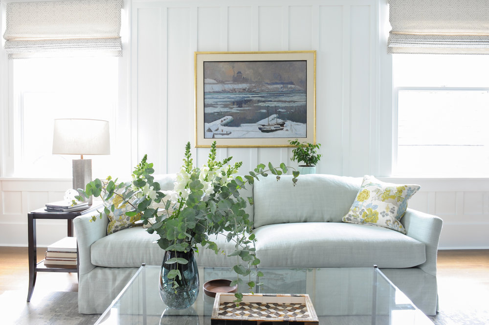A beautiful light grey couch and dark wood end table with a large glass coffee table in the foreground that has a tray table and a plant in a vase on it.