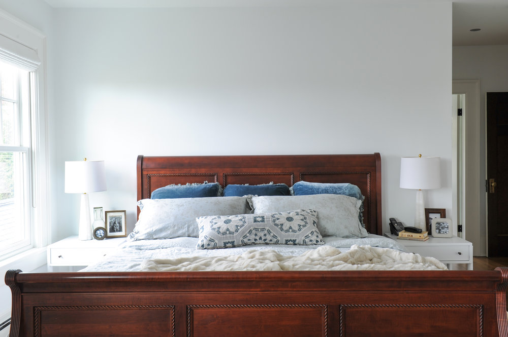 A rich dark wood sleigh bed with blue and grey throw pillows and white bedding sit between two white end tables. Black and white photos and a tall white lamp adorn both tables.