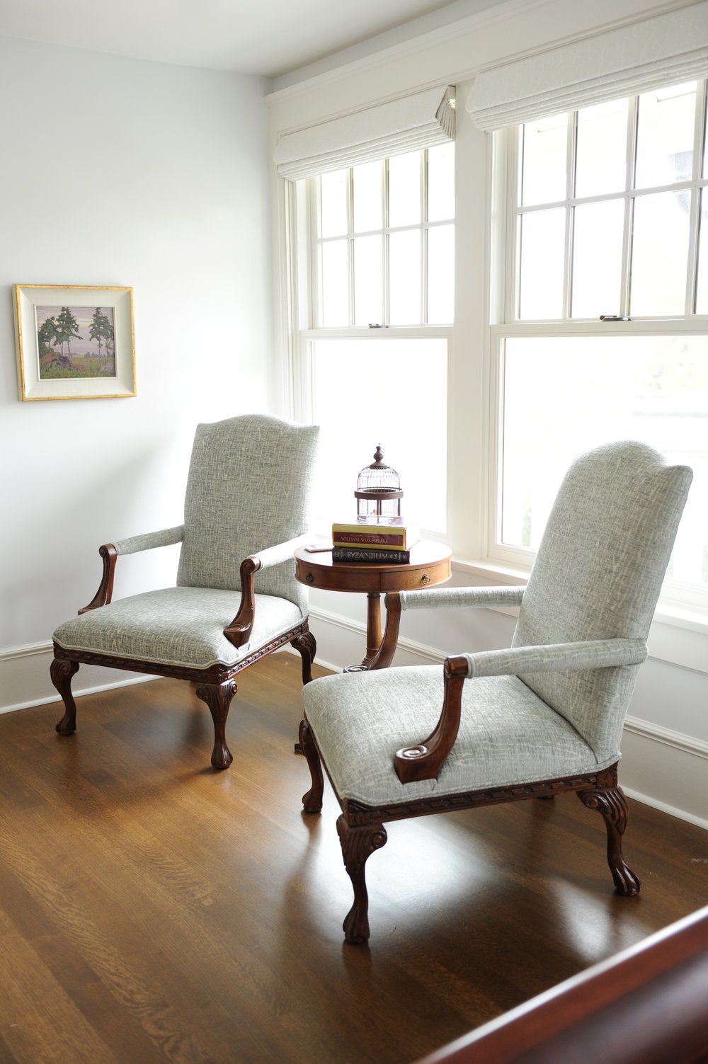 A round antique end table sits between two upholstered armchairs. A birdcage and a few books sit on top of the end table.