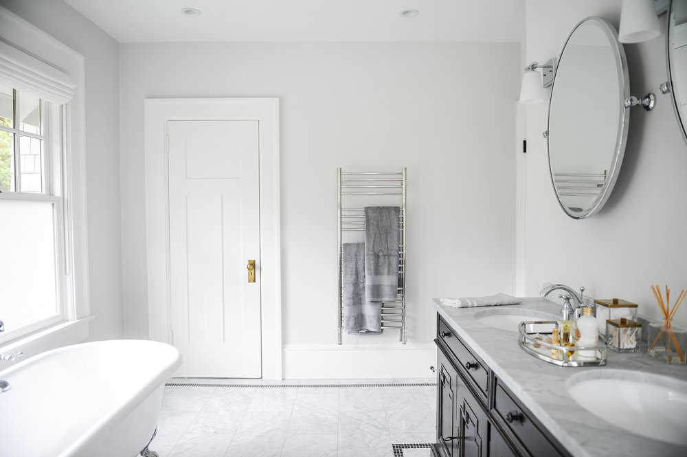 Double sinks in an antique drawer with round vanity mirrors located across from a white clawfoot tub in this bright bathroom with grey tiled floors. A towel warmer sits on the wall next to the door.