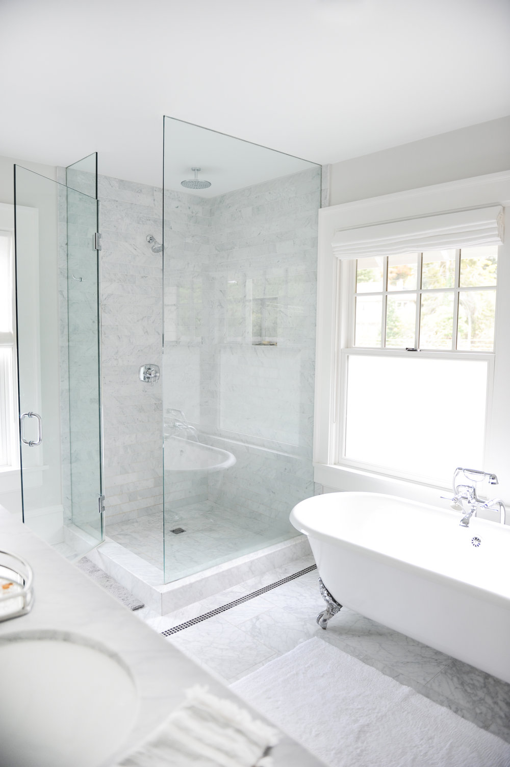 A tiled bathroom with a clawfoot tub and glass stand up shower with rain shower head sit beside a large window.