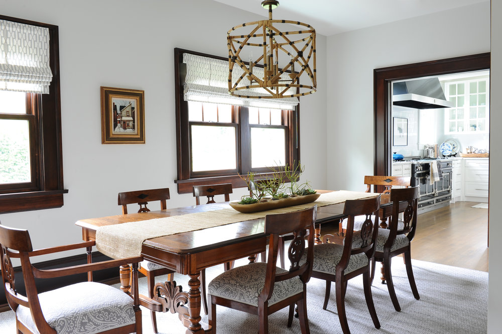 A large antique dining room table is surrounded by eight upholstered dining chairs. A tan table runner spans the length of the table with a wooden planter as the centrepiece. A wicker chandelier sits above the table.