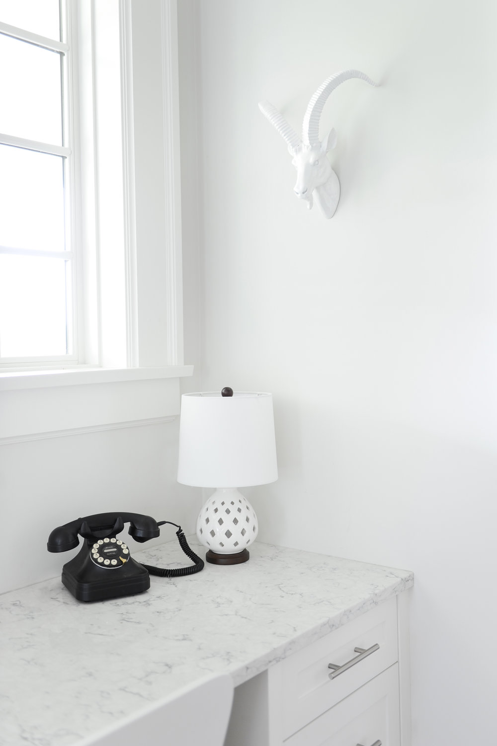An old-timey phone and a decorative white lamp sit in the corner of a desk. A white ceramic animal head hangs on the wall above it.
