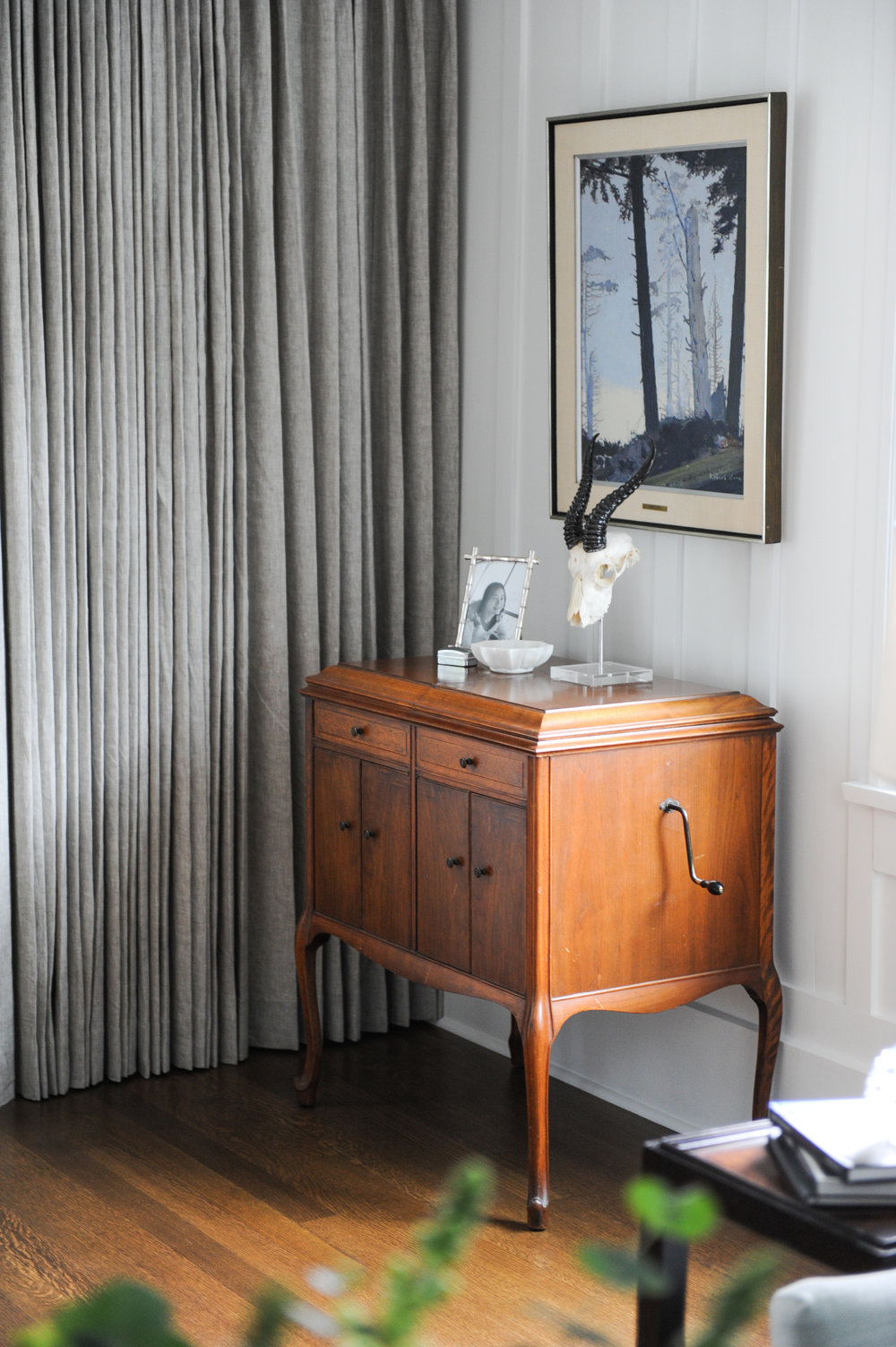 An antique crank phonograph converted into a cabinet sits in the corner of a living room. There is a frame of a family member, a ceramic bowl and an animal skull positioned on top. Hanging above it is a framed painting of trees.