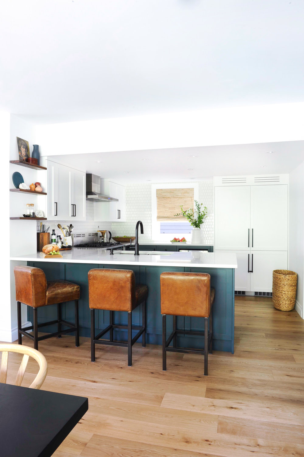Three leather kitchen barstools are positioned underneath the bar area of the kitchen, which is made up of blue counters.