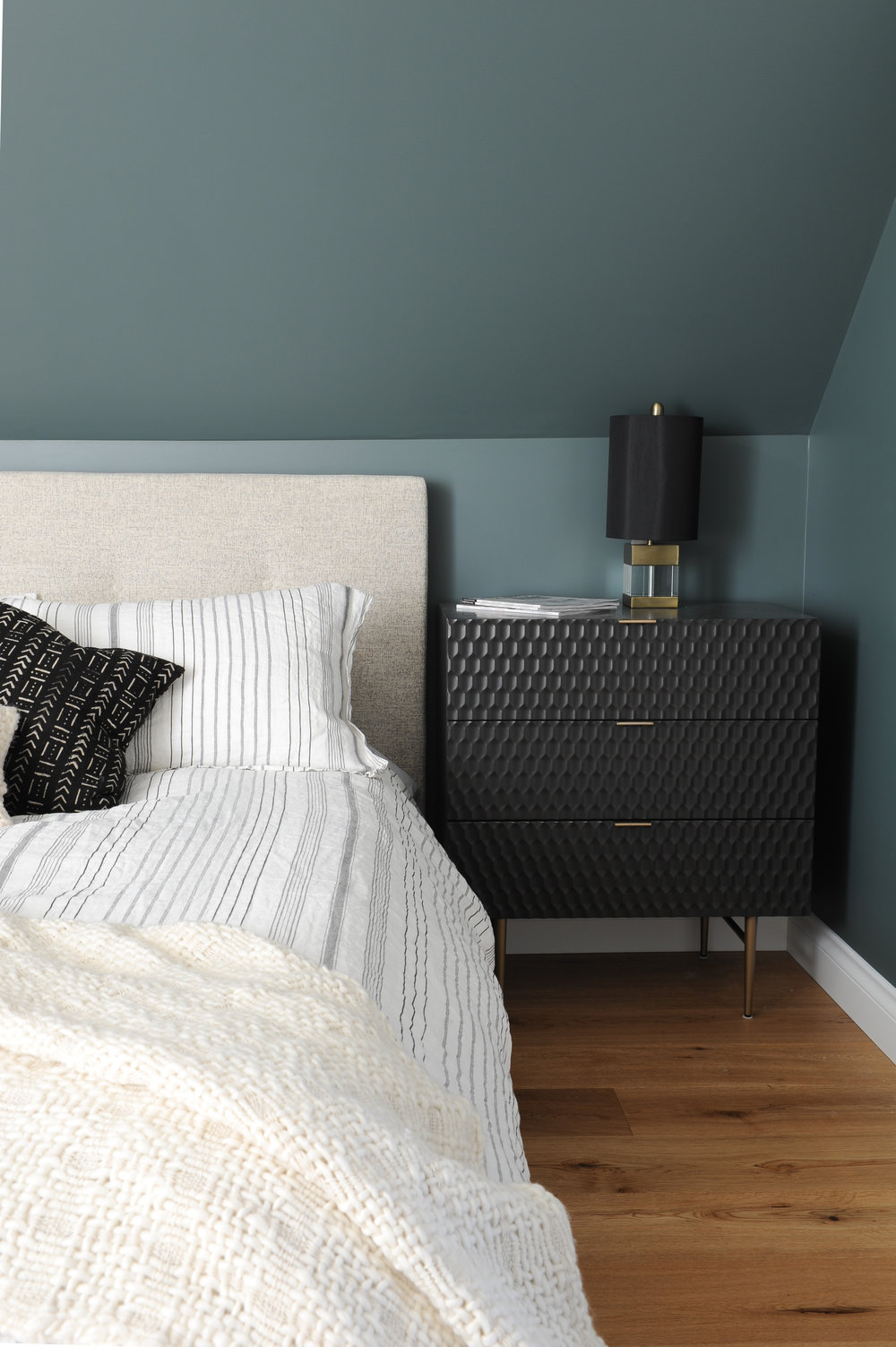 A black textured night stand doubles as a dresser, where a black lamp shaded light fixture sits on top, next to a bed with a tan coloured headboard and striped sheets.