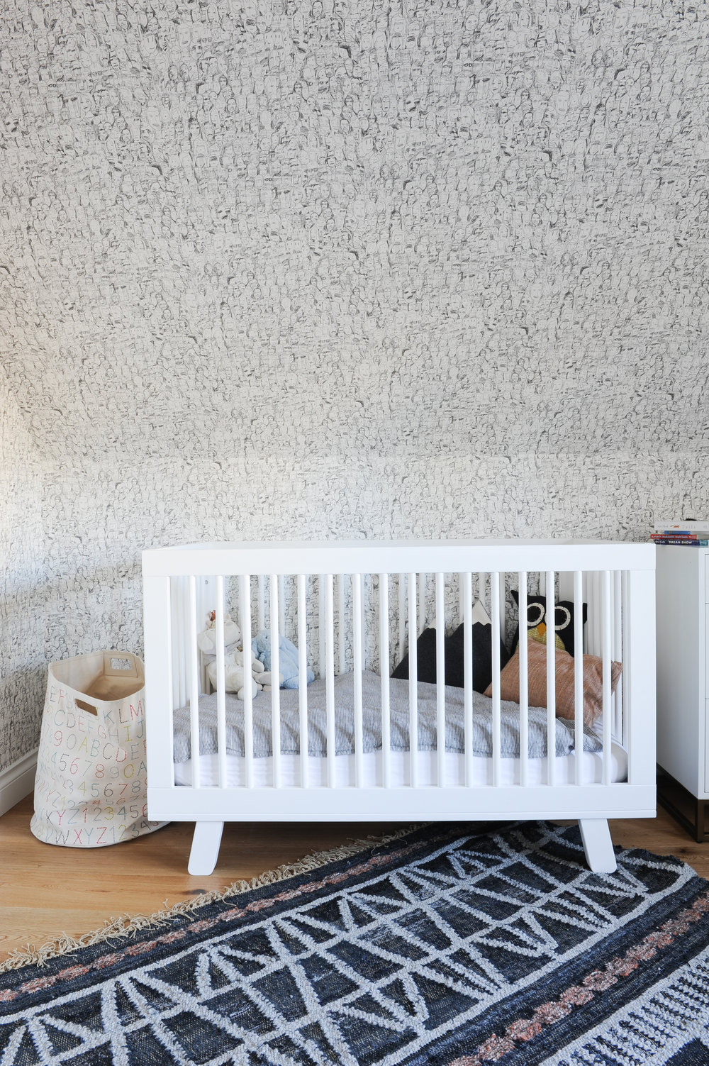A white crib sits in a children's room, decorated with speckled blue and white walls and large blue area rug.