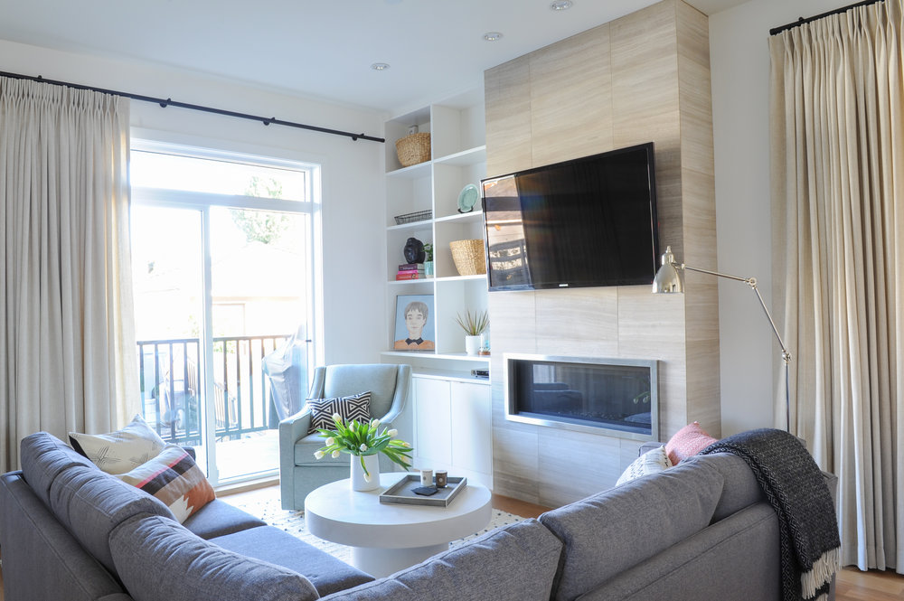 A comfortable home living room, including a large grey sectional and round white coffee table, plus a tan fireplace and a tv mounted above it, sitting next to a shelf with various home decoration.