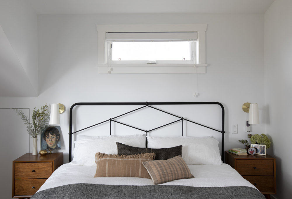 A large bed with metal framed headboard sits in between two wooden nightstands with a white and grey bed spread laid on top.