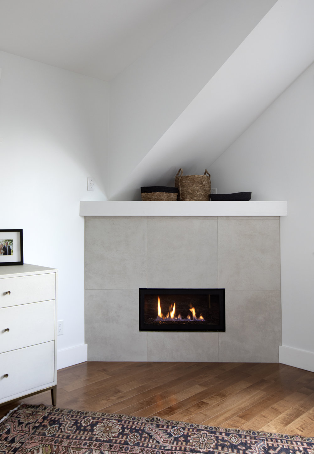 A fireplace set into the corner of the room is brightly let. Various wicker baskets sit on top of the mantel and a white dresser can be see to its left.