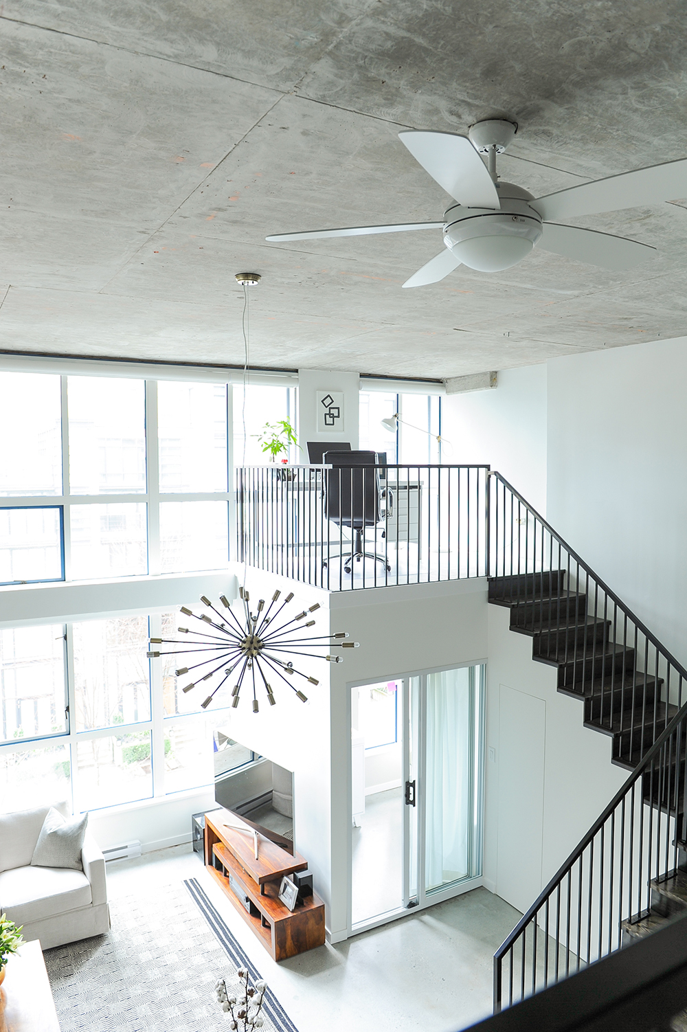 A spacious sunny loft space with white rooms and a black staircase leading from the living room up to the office space.