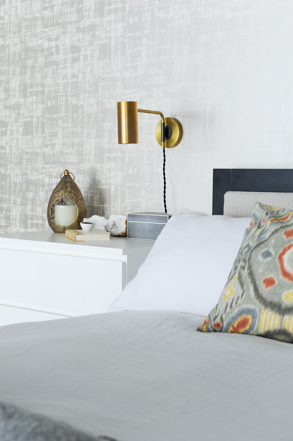 Some interesting decor, such as a candle, a book and quartz rocks sat on a white dresser drawer bedside table with a gold light sconce fixed into the wall, beside a black and tan bed with white bedding.