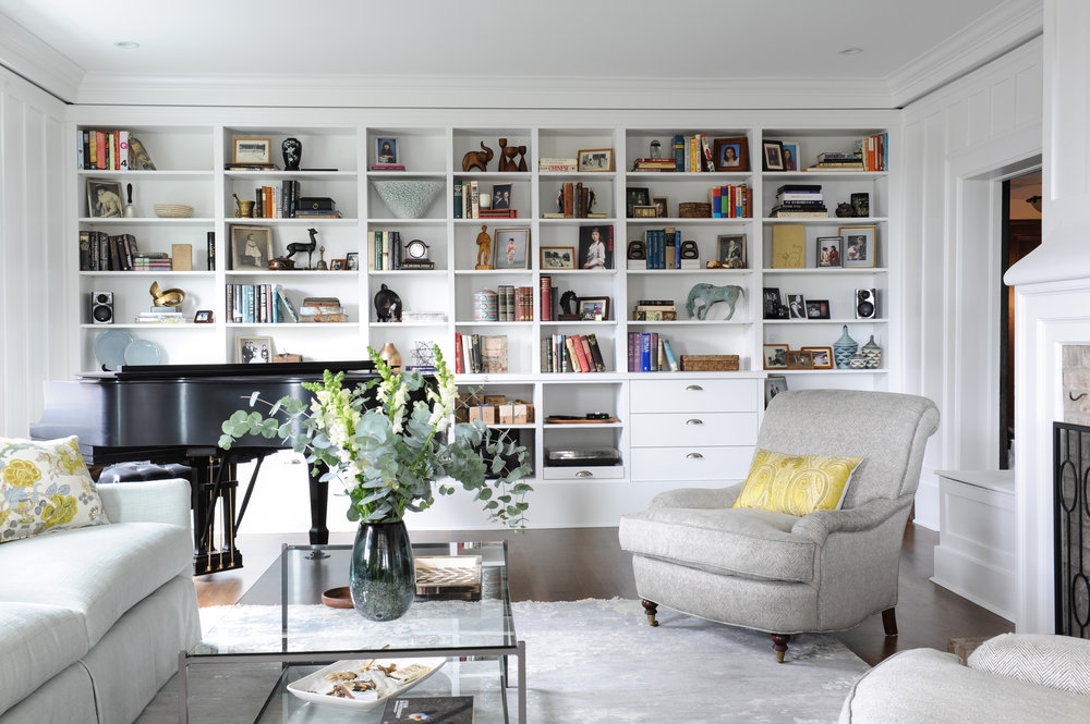 The entire wall of this living room has been fitted with shelves to display various antique treasures, picture frames and books. In front of it sits a baby grand piano and living room furniture.