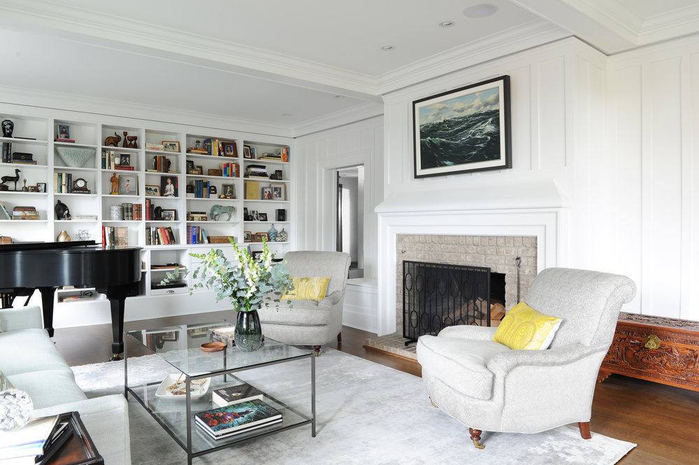 An affluent looking living room, complete with a baby grand piano and an accent wall made up entirely of shelves, displaying various antique treasures and books, surrounds a stone fireplace and living room furniture.