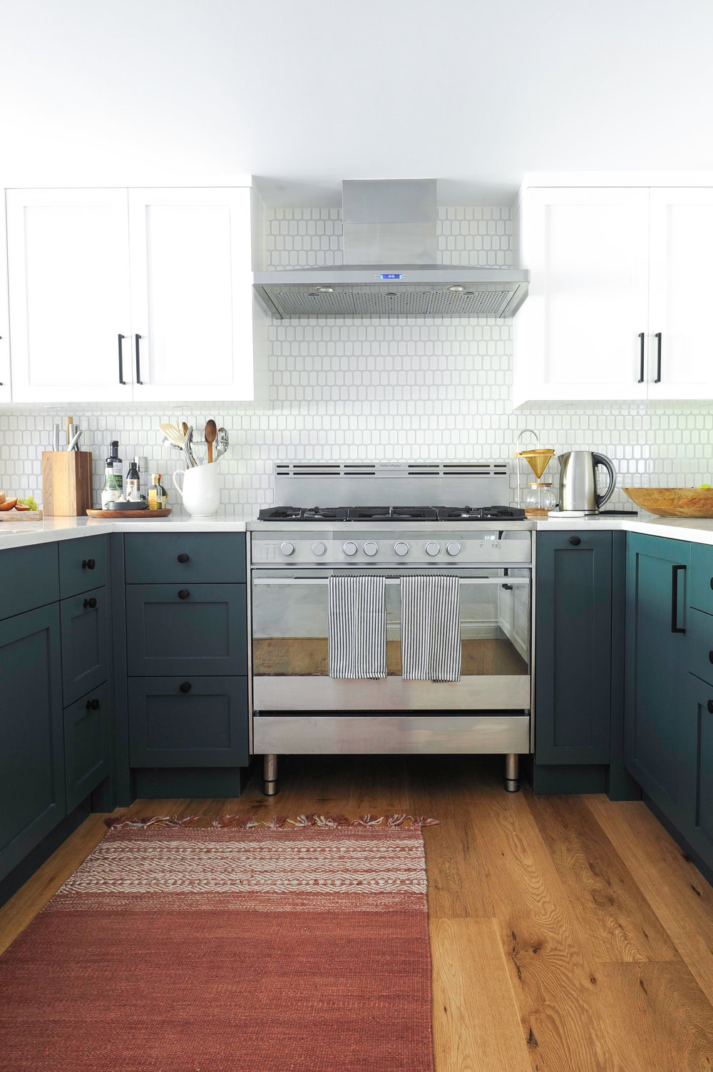 The kitchen centres around the stainless steel gas cooker and range hood, displayed against the decorative white tiles and blue cabinets.