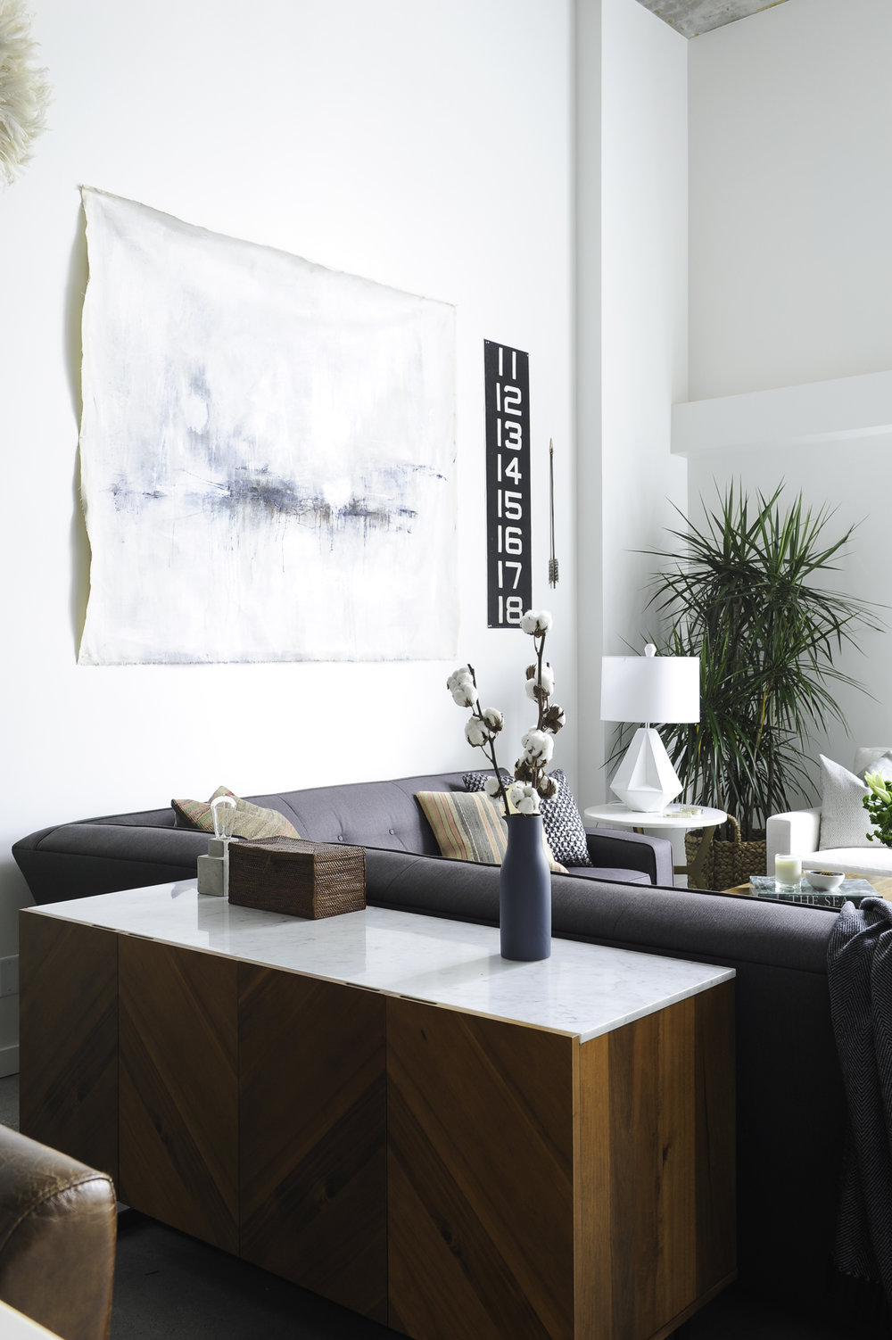 The sunny living room of the Seymour Street loft including a grey couch and teak furniture in downtown Vancouver, BC.